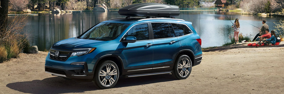 2021 Honda Pilot parked by lake with family